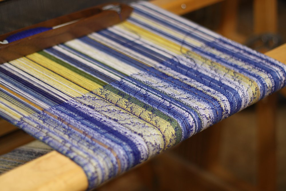 A lacy weave spills across a warp pinstriped in blue and white and yellow | 14 Mile Farm Handweaving