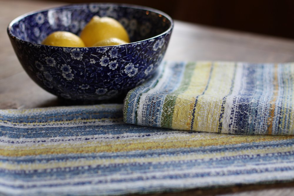 A pair of classic farmhouse tea towels in yellow and blue and white rest on a worn wooden table with a bowl of lemons | 14 Mile Farm Handweaving