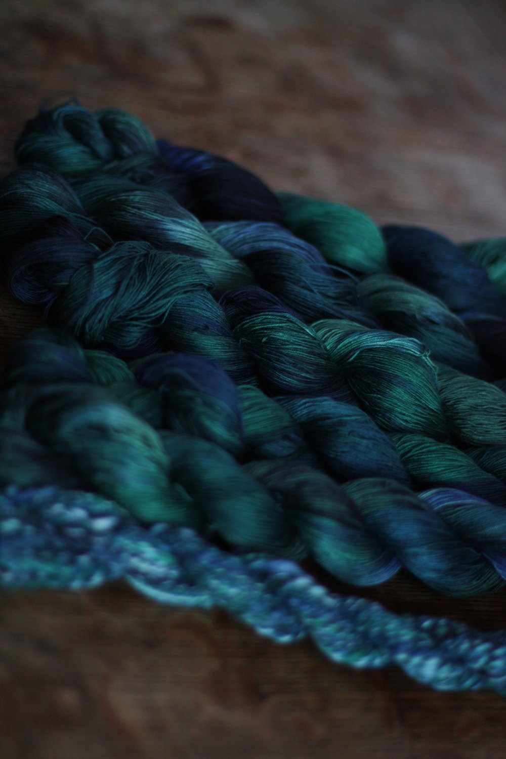 Skeins of Seacell dyed in moody blues and greens and teals and blacks rest on a wooden table | 14 Mile Farm Handweaving and Homesteading