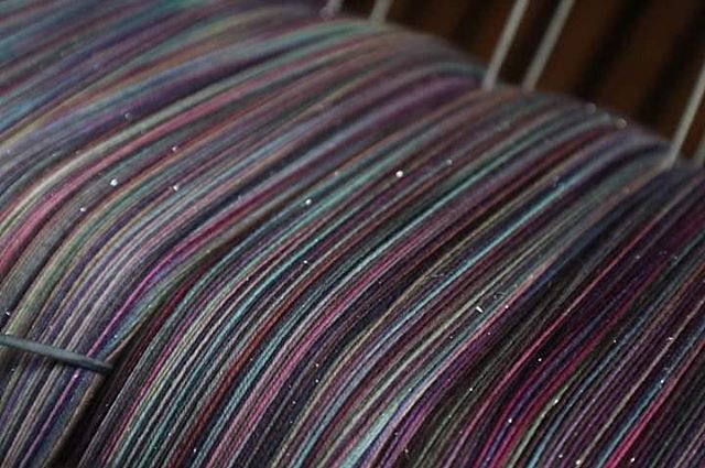 Prismatic Healing is on the loom at @stormborne_fiber_witchery. Sparkle Supima from @saltwaterrosethreads really shines in this moody rainbow warp. #sparkle #prismatichealing #saltwaterrosethreads #wovenwithloveandmagic #cauldronandcloth @cauldronandcloth #handwovenbabywrap #handwovenwrap #babywearingwrap #loomtowrap #l2w @loomtowrap #babywearing #closeenoughtokiss #attachmentparenting  #carrythem #babywearingweaver #visibleandkissable #babywearersofinstagram