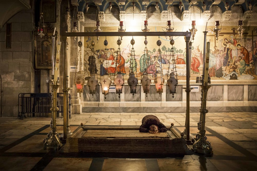 A Christian pilgrim prays on the stone of unction in the Church of Holy Sepulchre in Jerusalem's Old City.