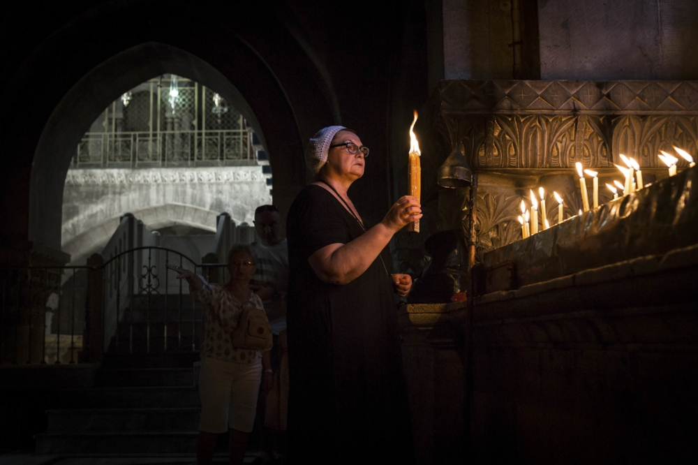 A worshipper light candles near the Calvary of Golgotha in the Church of Holy Sepulchre in Jerusalem's Old City.