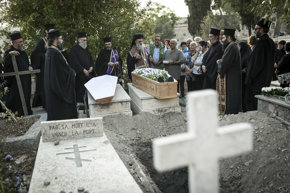 Greek Orthodox clergyman and mourner of the Greek Orthodox Community at a funeral of one of the community members.
