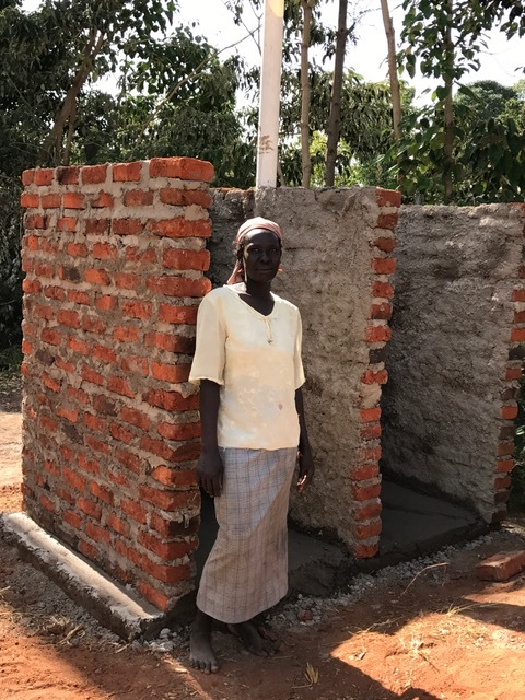 Agness next to her new outhouse and bathing area. All the neighbors have been coming over wondering what is going on. They are amazed that a widow would be helped. It's all because of Jesus Christ!