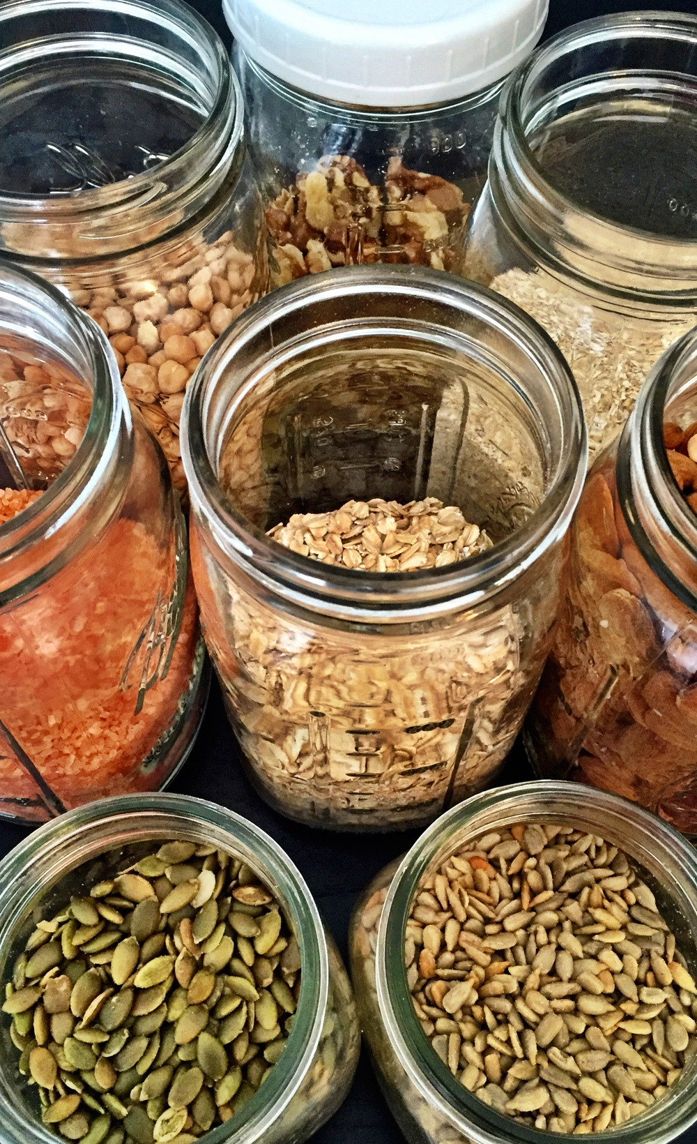 Some of the staples currently on hand in our kitchen. walnuts, oat bran, almonds, sunflower seeds, pumpkin seeds, Hawaiian sea salt, garbanzo beans, rolled oats.  (Clockwise from top)