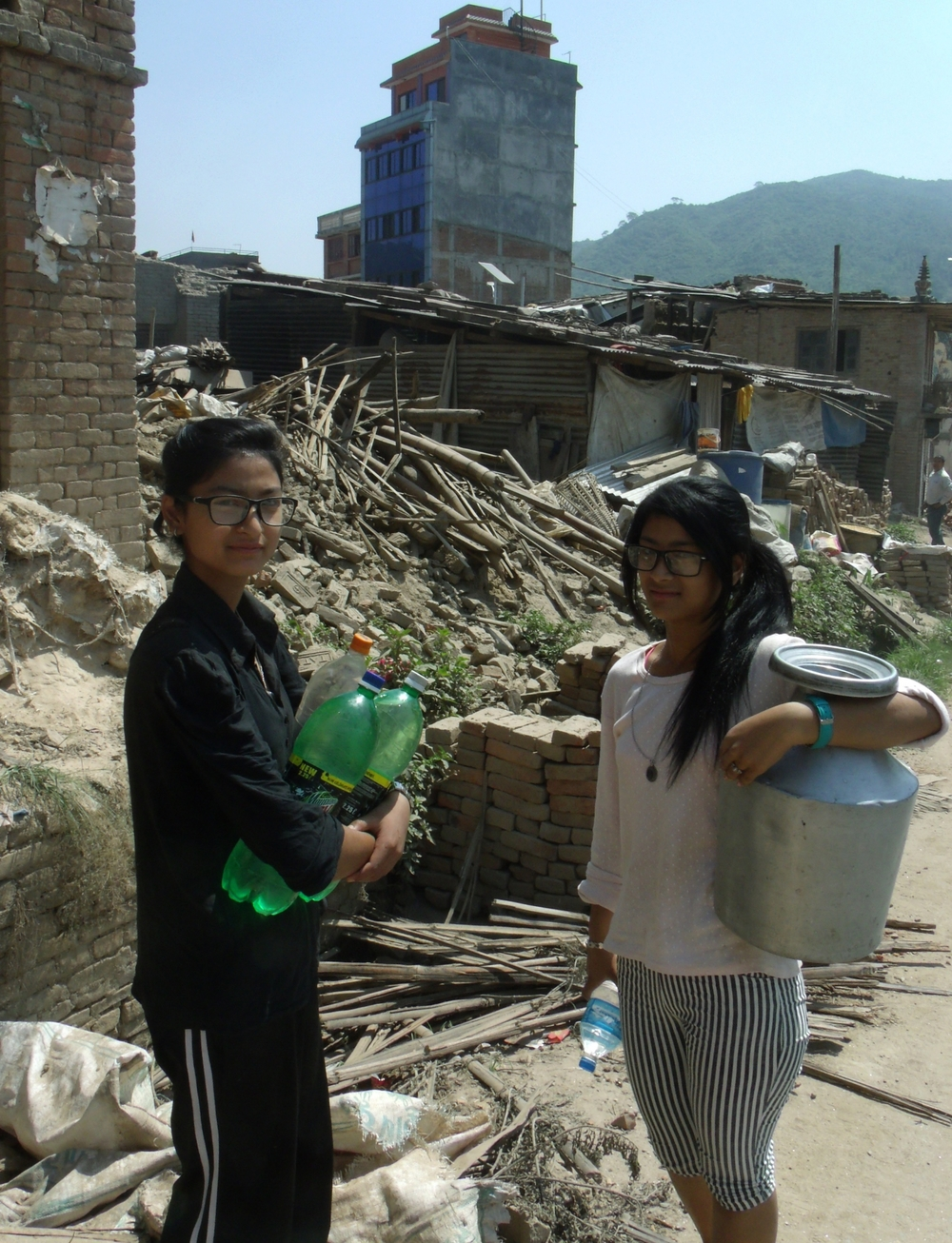 Girls carrying water back from a tap outside their collapsed home
