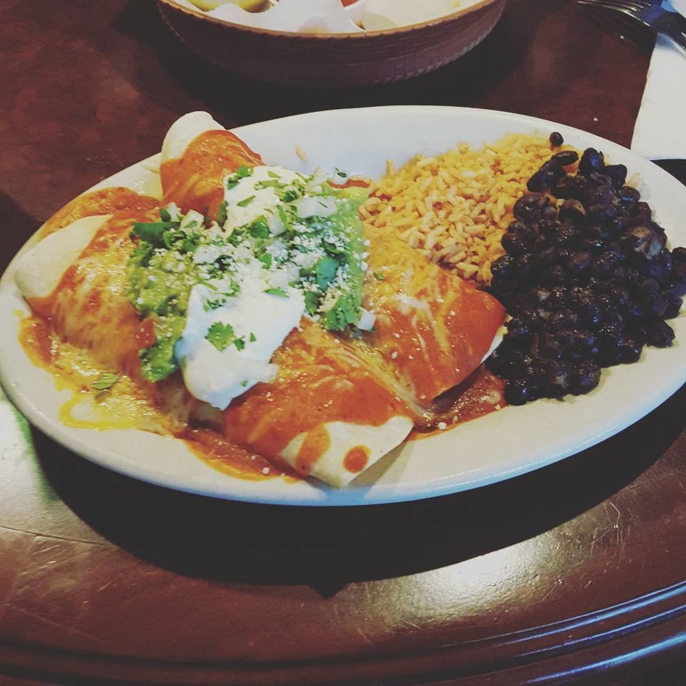 Enchiladas topped with traditional red sauce served with a side of rice and black beans.    Photo Credit:  @woodendalehomestead
