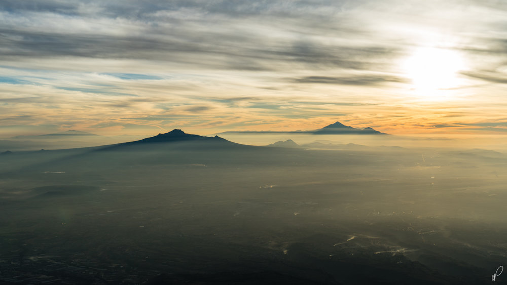 What a priceless sunrise. Pico De Orizaba in the far back with La Malinche ahead rising over Mexico's infamous pollution. As seen from the Summit of Izta.