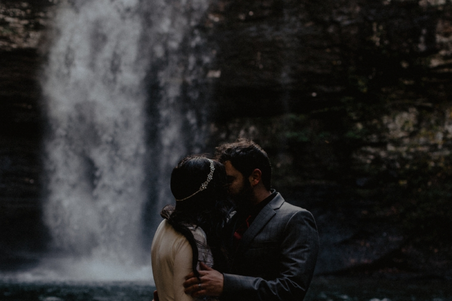 elopement wedding couple hugging and kissing in front of waterfall at cloudland canyon in north georgia as wind blows