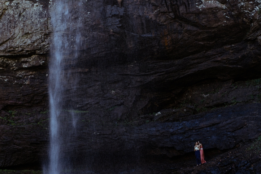 same sex couple hugging and snuggling under a waterfall in romantic photo at cloudland canyon in north georgia