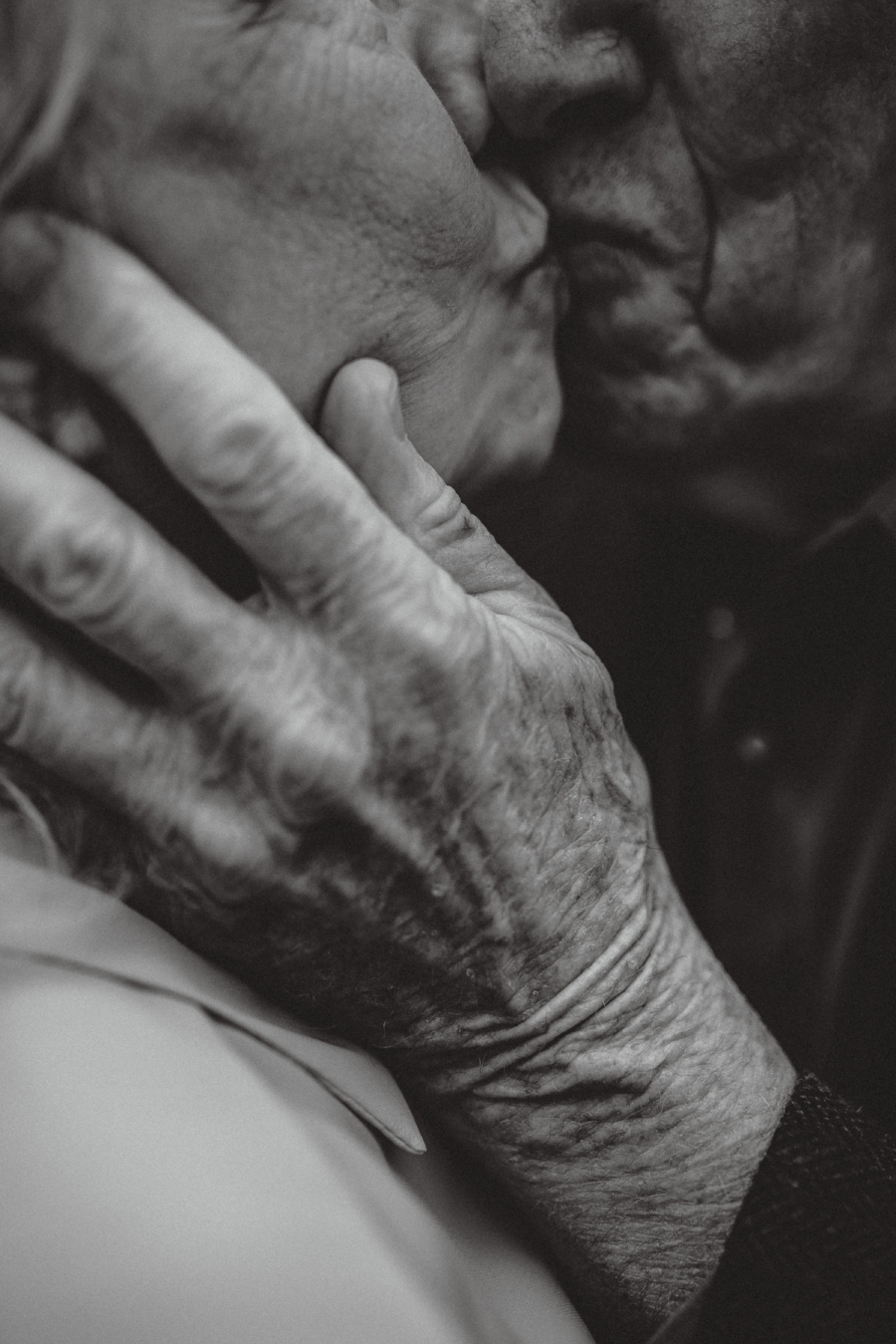 dark and moody romantic photo in black white of elderly couple grandparents kissing close up