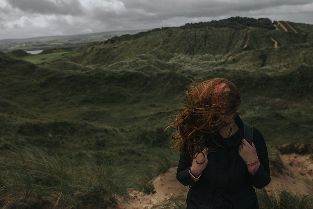woman with long red hair blowing in the wind as she hikes the dunes at portstewart strand in northern ireland while wearing vinta camera bag