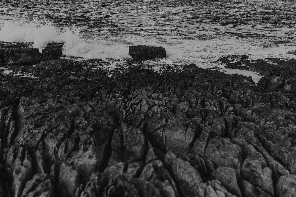 black and white photo of jagged rocks along the northern ireland coast with water rushing over them by meri daugherty