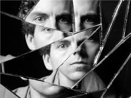[image description: A black and white photo of someone's reflection in a broken mirror. The person's face is fractured and segmented along the lines of the broken glass. The whole face cannot be seen in any single chunk of class--only parts. Source unknown. Photo found  here .]