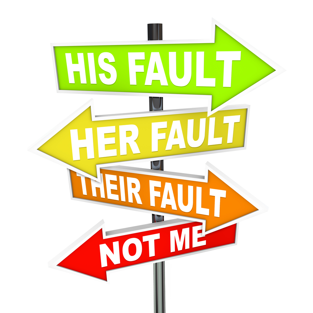 "[image description: a graphic of a sign post with four different signs. Each sign is an arrow, pointing in a different direction. At the top is a green arrow inscribed with ""HIS FAULT"". Next is a yellow arrow inscribed with ""HER FAULT"". Next is an orange arrow inscribed with ""THEIR FAULT"". The last arrow, at the bottom, is red and states ""NOT ME"". Image found on Google Images.]"