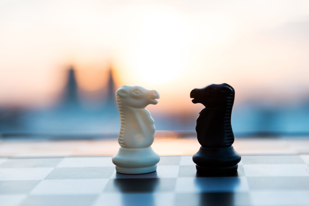 [image description: Photo of two chess pieces facing each other. On the left is a white knight, on the right is a black knight. A blurry city-scape is visible in the background. The chess board is visible beneath the pieces. Photo by baona/iStock / Getty Images]
