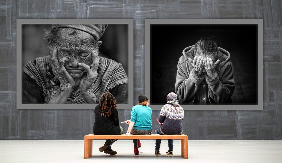 [image description: photo of three people on a bench, facing away from the camera, and facing towards to large photos on a wall, as if at a gallery. The two photos on the wall are of individual people, head dropped, hands covering their faces.]
