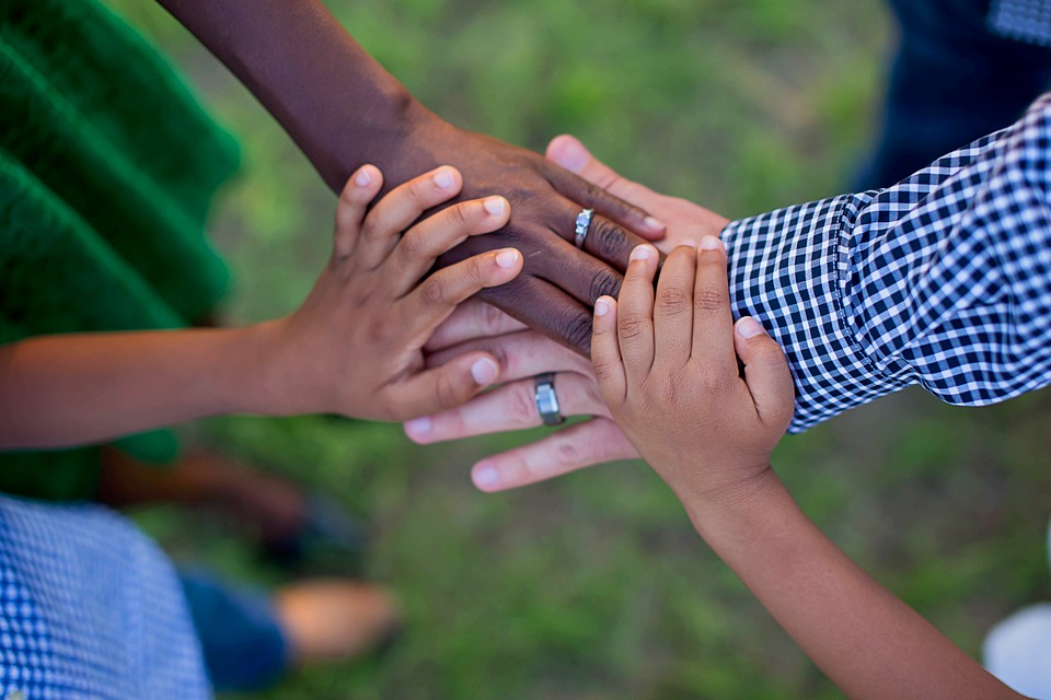 [image: aerial photo of four hands placed on top of each other. The background is a blur of green and clothing colors, indicating that the four people are standing in a circle together. Two hands are larger with wedding rings and two are smaller, indicating that they belong to parents and children in a family.]