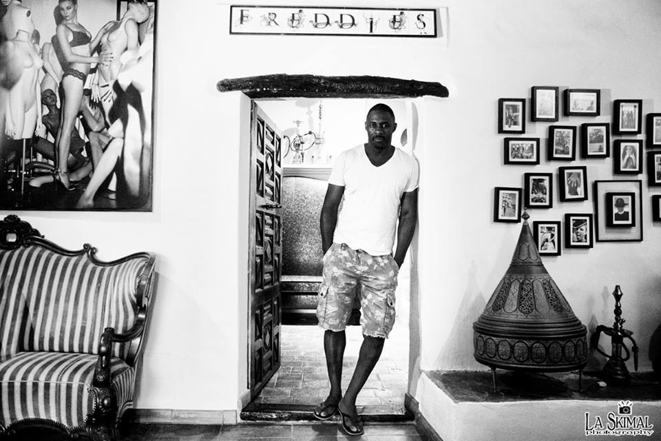 "Actor Idris Elba standing in the infamous Pikes Hotel aka ""Ibiza Rocks House at Pikes"". Pikes commissioned me to create 40 art pieces for the hotel. On his right is ""Mannequin Master"". PhotoCanvas & acrylic 40x60in. And on his left are many smaller framed pieces. For sales and acquisitions please contact me."