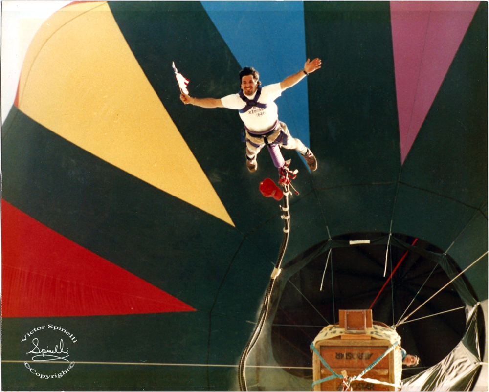 Photo of the Day:  1992 was the year I became a commercial hot air balloon pilot and in this photograph you see me bungee jumping out of my balloon. It was probably testing the system before any clients to the leap. At the time there were only about 12-15 balloon bungee jumping companies in the world. The next year I was taking sky divers up to 10,000 ft to leap from this balloon. ©Victor Spinelli Archive