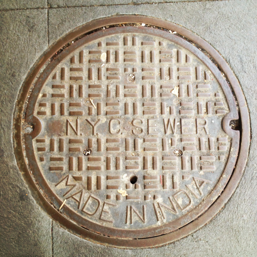 NYC sewer manhole covers. Made in INDIA. It baffles me why we would import a 35 kilo manhole cover from India. Ok, it's probably cheaper than to manufacture here with shipping included however the spent fuel and pollution to ship them is worse for the earth in the long run. And this does not account for India's lower pollution controls at their factories. At the least we could have them mold a nice design on them. I say by locally, New York City.