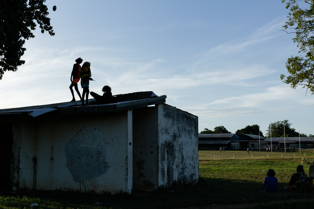 Children playing on an as others watch the local derby match. Image by Hugo Sharp.