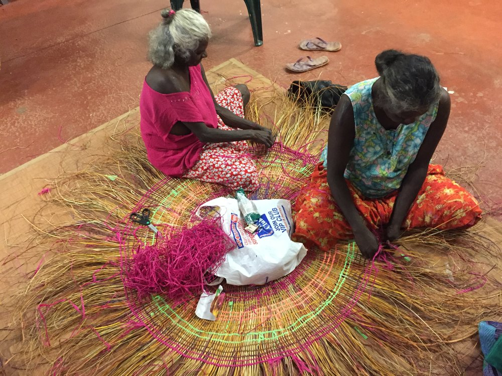 Maisie Mirinwarmnga and Vera Cameron coming behind, weaving mat commission. Photo Mandy Martin.JPG