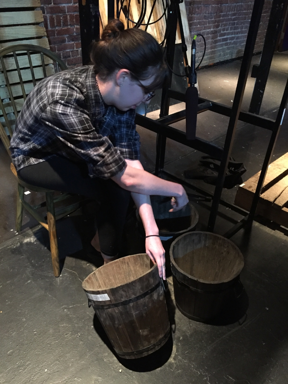 Props assistant Alexis Retcofsky preps rock buckets for the next performance