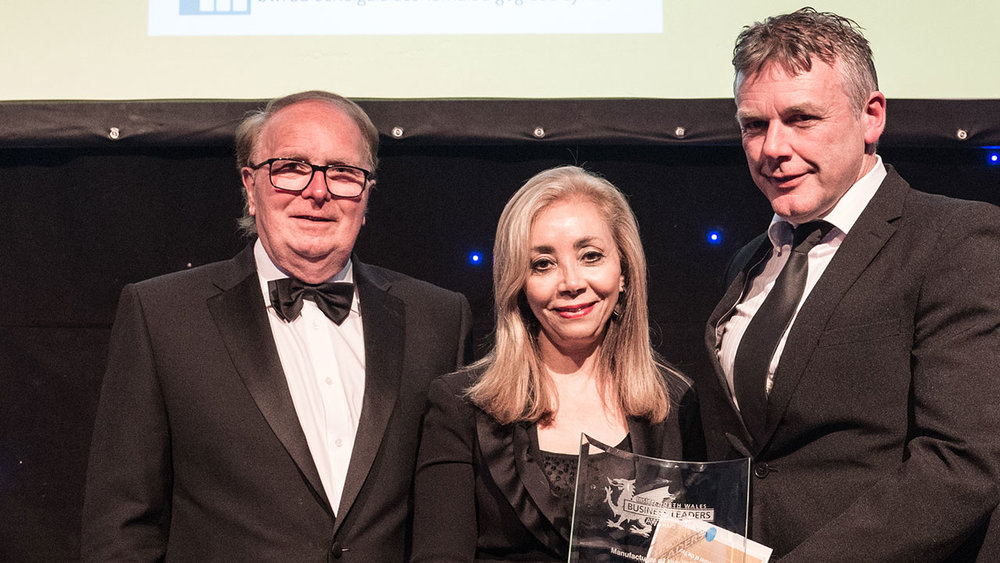 Photo: Leyla Edwards (CEO) & Graham Jackson (Chairman) collecting the award for Manufacturer of the Year presented by Iwan Trefor Jones (North Wales Economic Ambition Board)