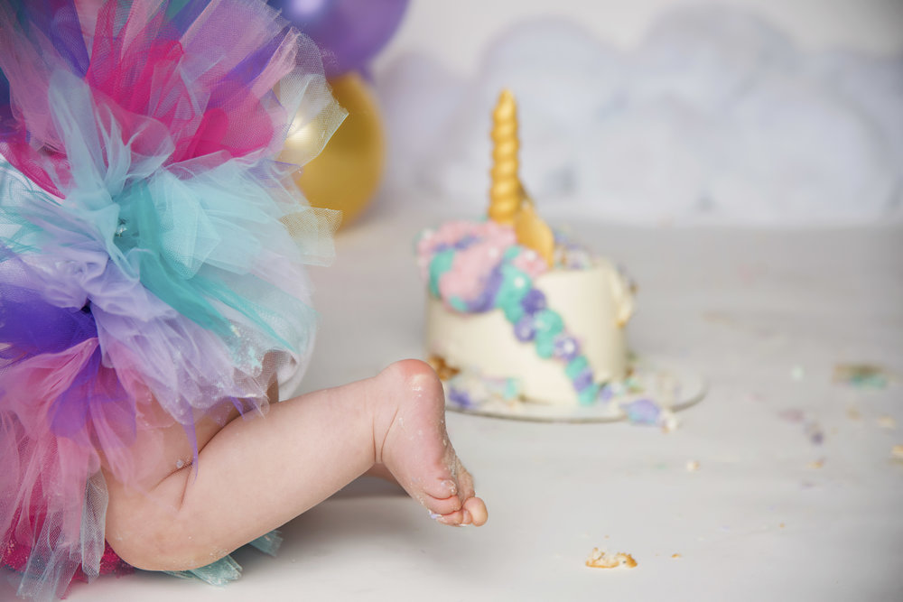Cake Smash Unicorn Cake Stephanie's Cupcake Company Remember When Portraits Cincinnati Photographer Little Girl Crawling Away from Cake