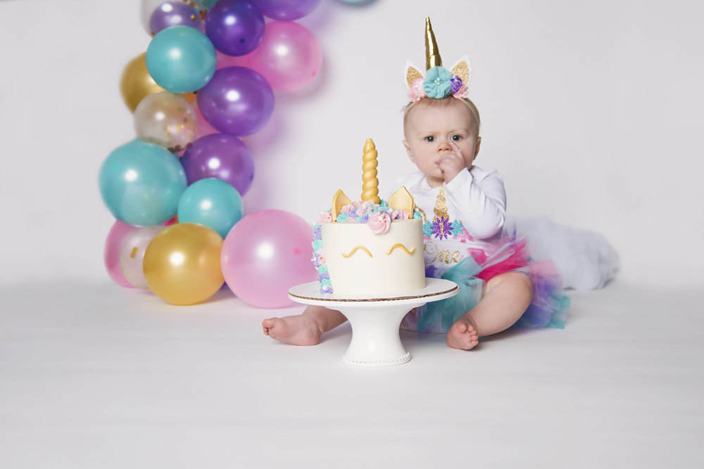 Cake Smash Unicorn Cake Stephanie's Cupcake Company Remember When Portraits Cincinnati Photographer Little Girl Enjoying Cake