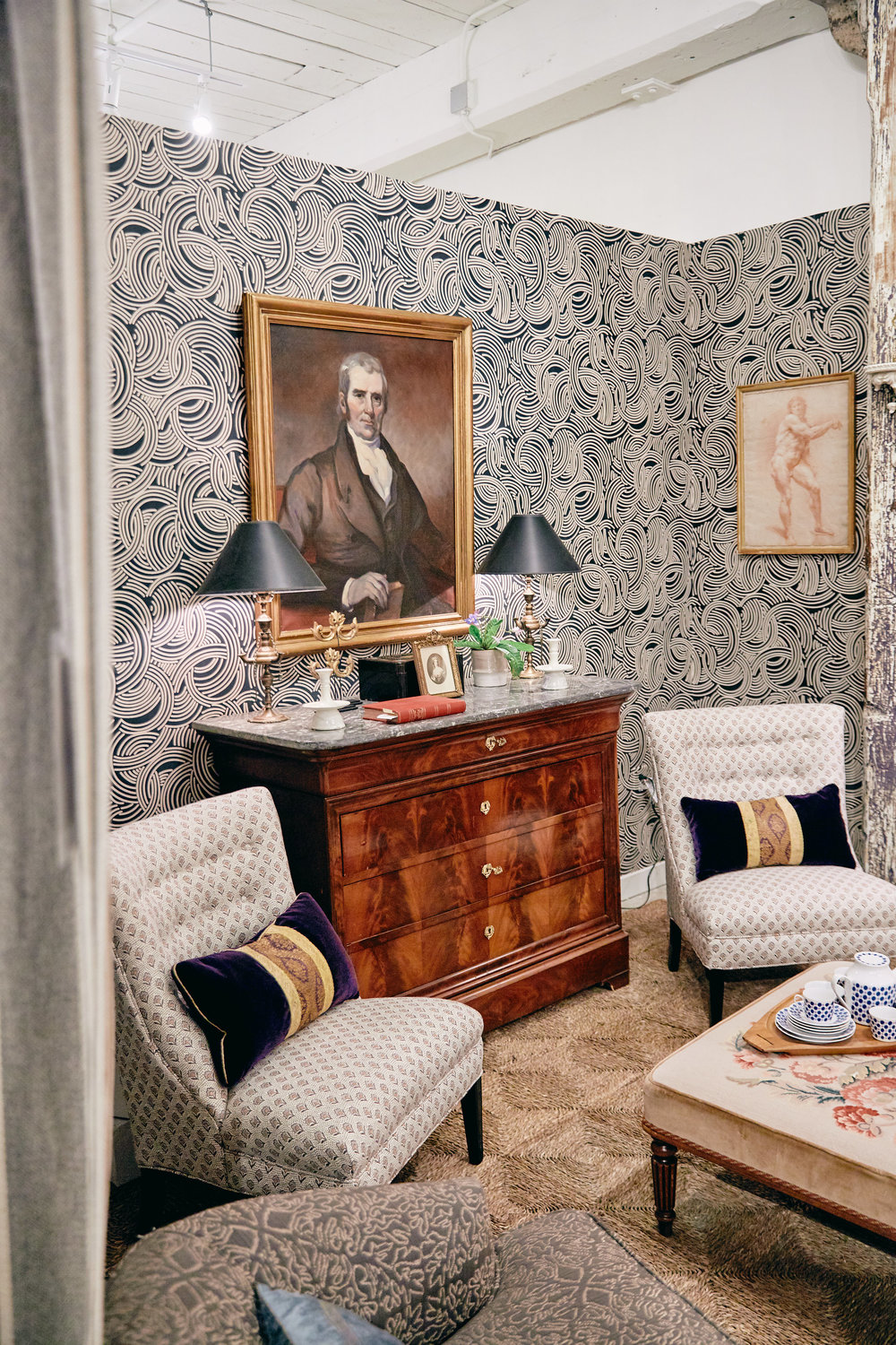 The Tourbillon Wallpaper from Farrow and Ball creates a graphic backdrop for the slipper chairs covered in Lewis and Wood linen.  The 19th century commode is from John Pope Antiques and the portrait is from 17 South Antiques.