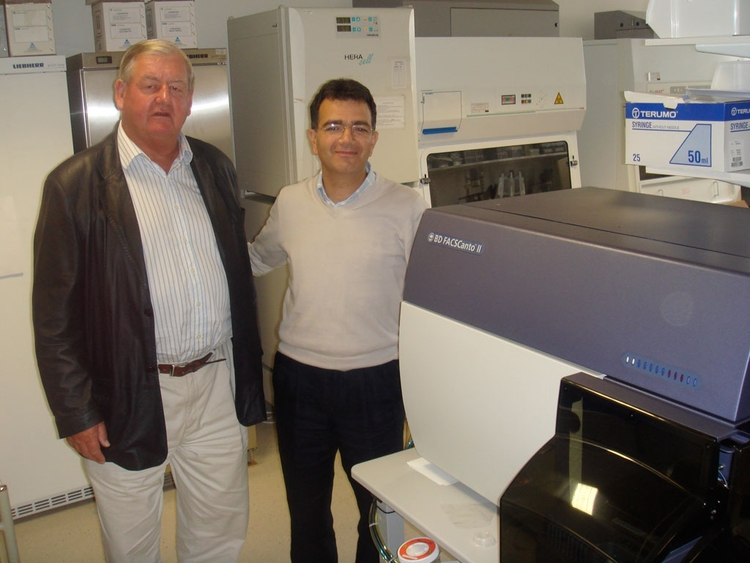 Trustee Donald Legget admires the FACS Canto ii analysis equipment, partly funded by the HMCRT, with Prof. Enzo Cerundolo