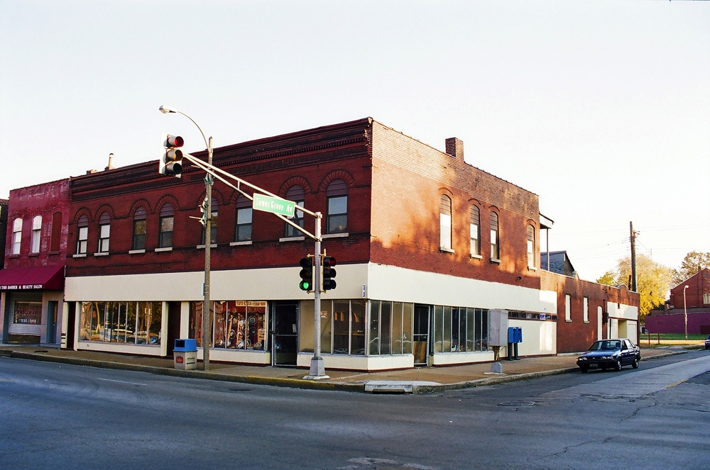 The Mangrove Building circa 1999. Historic windows and   storefronts had been removed. Chain-link gates and locks made the building uninviting.