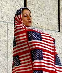 Shida Pegahia in a chador woven from small American flags, designed by Gita Kashabi.