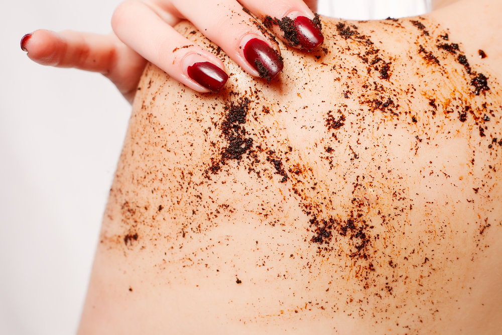 Brunette woman cleans the skin of the body coffee scrub
