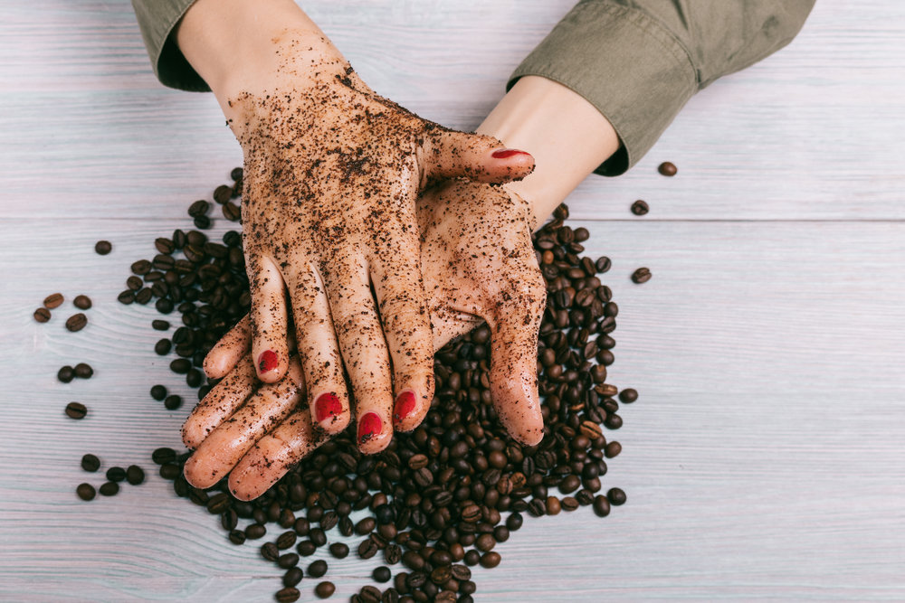 Woman applies coffee scrub on hands