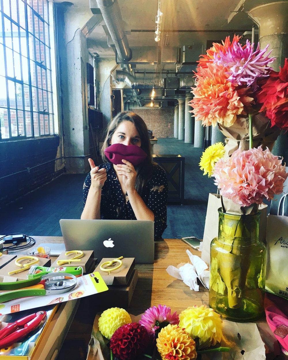 Caroline cheesing among floral props, editing photos.