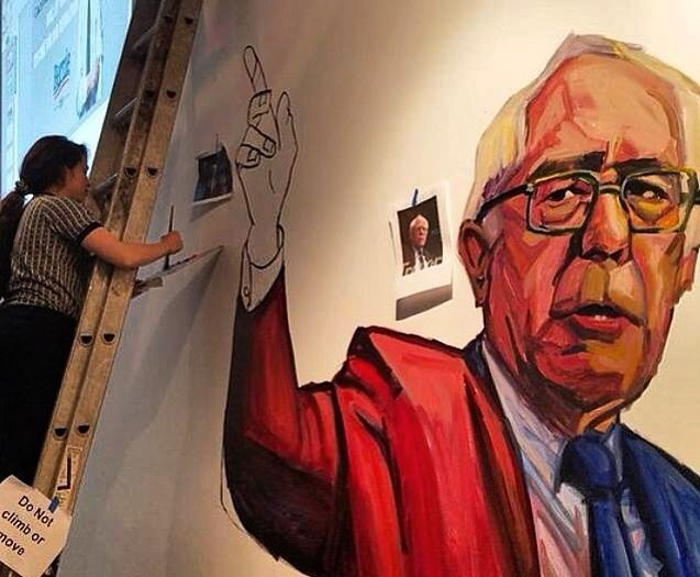 Paige Emery  paints a mural of  Bernie Sanders . photo by Paige Emery; via  The Guardian