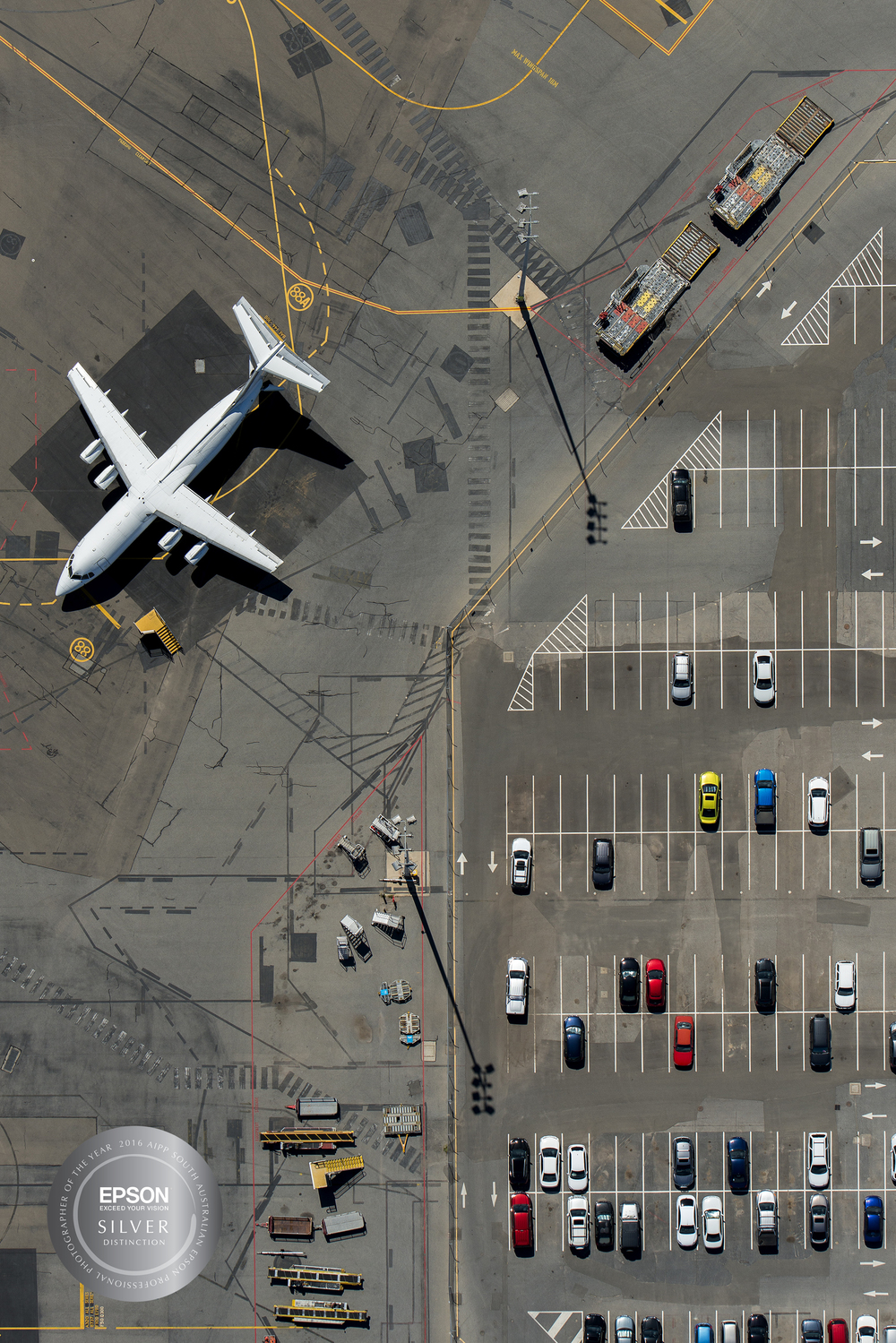 The long term car park at Adelaide Airport with a  BAE146  aircraft. When flying at 500ft in a helicopter everything happens very fast below, you really trust your instincts for framing and subconsciously 'seeing' - this was captured during a charter to photograph the new solar installation on the roof of the Adelaide Airport carpark as well as various sites around the airport precinct for both  Solgen  and the airport . I really like the strong opposing shadows from the floodlights (and the cars that look like Matchbox toys!). Shot on a Nikon D800 and processed in Lightroom and Photoshop.