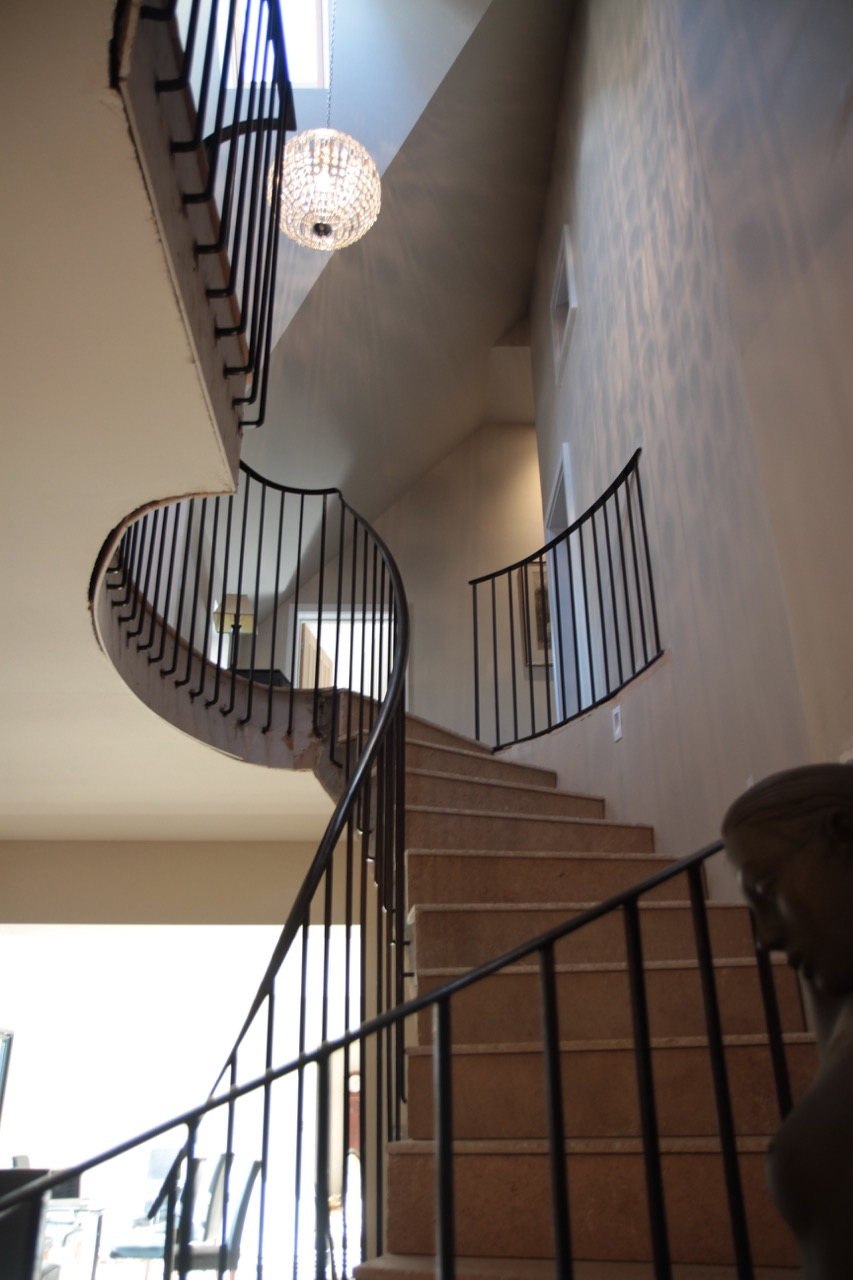 Stone elliptical stairway supported by suspended reinforced concrete floor with bespoke steel balustrades