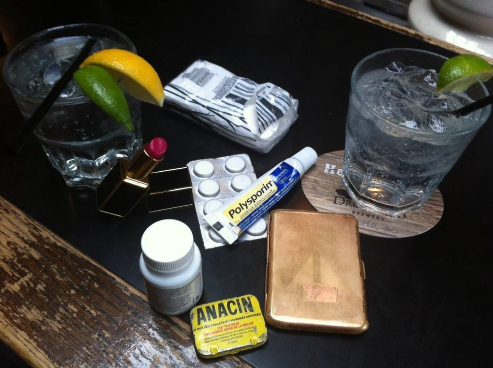 "Probably funnier in our own heads, but one day at Barney's we decided to empty pockets and purse onto the bar and make a photo diary entry.  Titled ""Tears, Regrets and Recriminations"" this brought to life a couple of the characters we invented.  Brent was my physician Dr. Penis Morningwood, and I was his doddery, frail and vain Dowager patient in constant need of attention and medication in the form of ""tinctures"", which were administered to me whenever I would become hysterical.  Thus, the old Anacin tin which Brent always carried, next to my Advil and other ""medcin's"", including booze.  Well, we thought it was hilarious..."