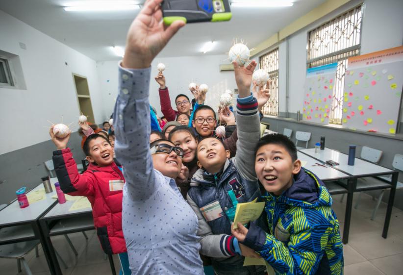 """Cristina tomando un """"selfie"""" con un grupo de estudiantes que construyeron sus propias planetas con satelities en un Campamento STEM en Beijing, China - Enero 2017"""