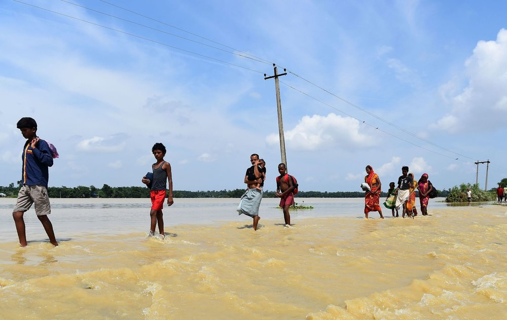 Crossing through flood water in Tilathi, Nepal, last week. CreditPrakash Mathema/Agence France-Presse — Getty Images