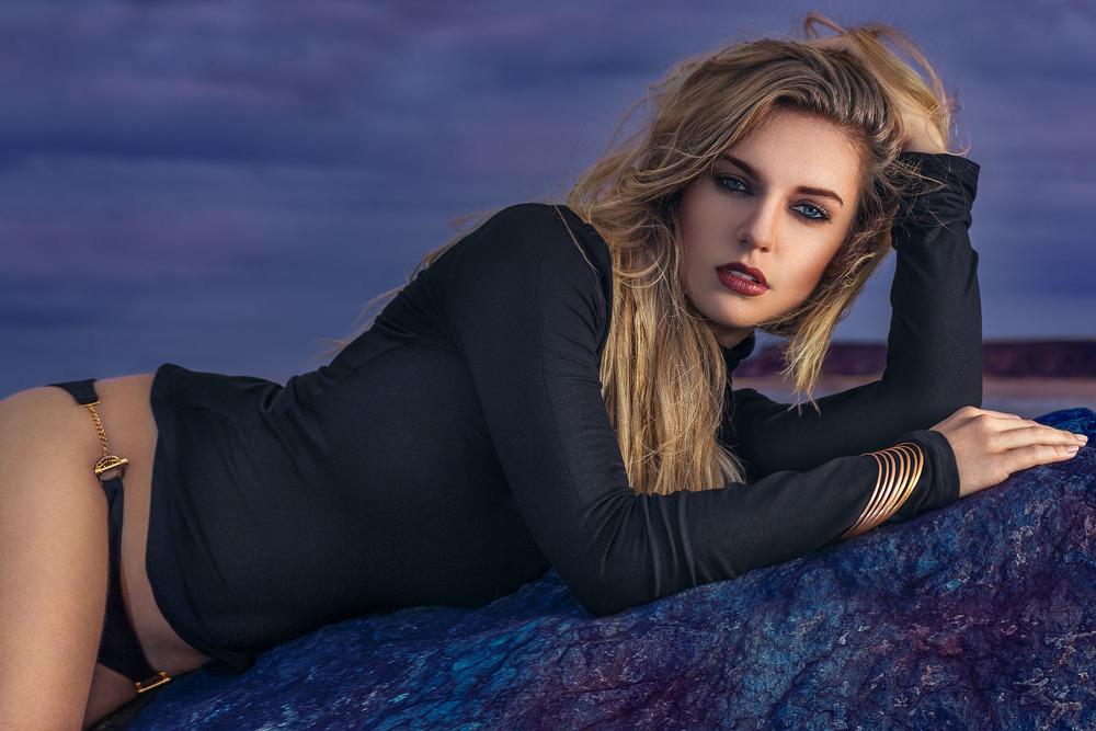 Female model lying on blue Happisburgh beach rocks at sunset wearing Aurum Jewellery bracelets