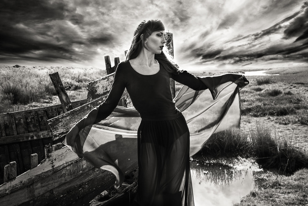 Female model wearing black dress at a Norfolk boat wreck with a dramatic sky