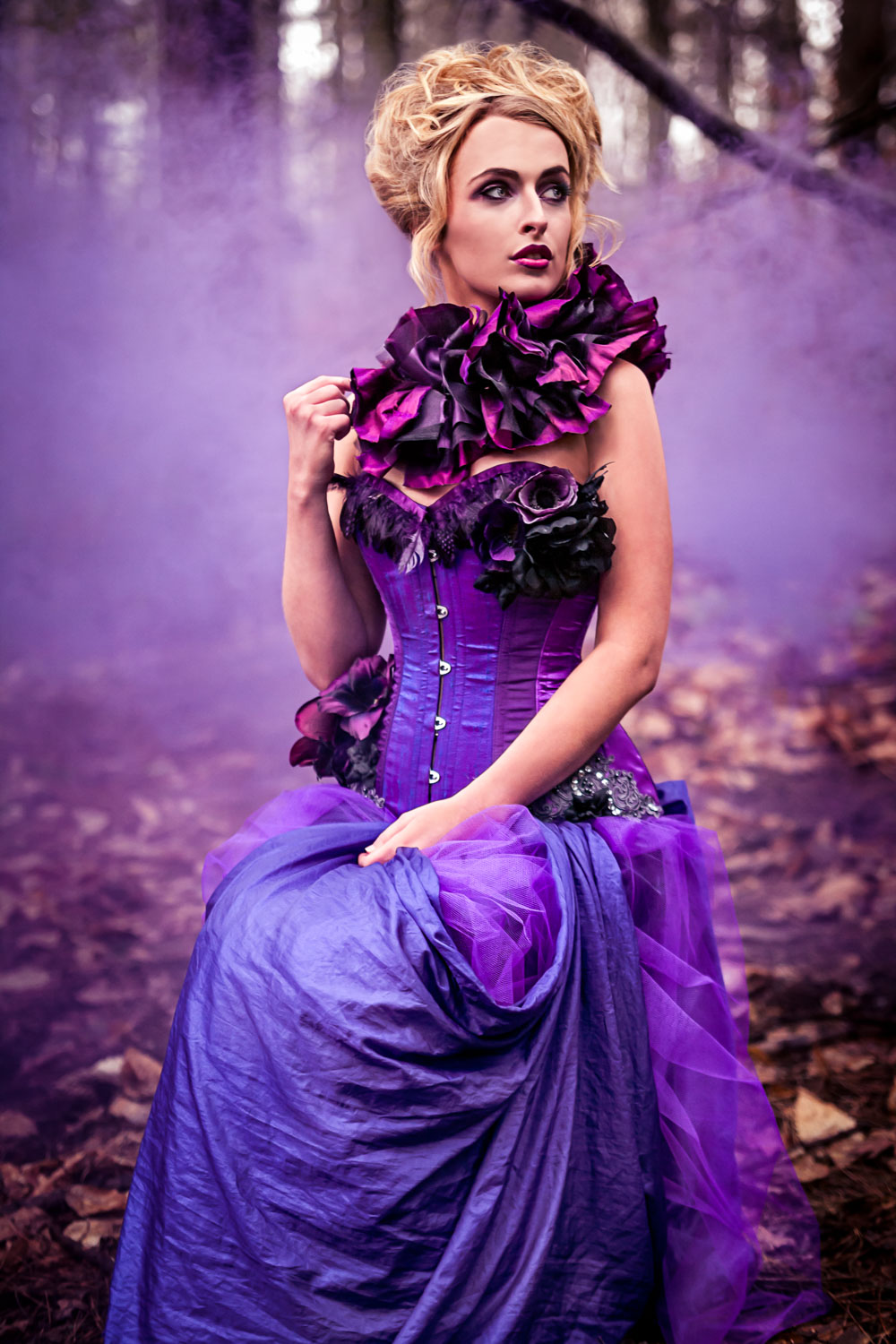 Female model dressed as a purple rose wearing a purple corset and neck ruffle in an enchanted forest with purple smoke