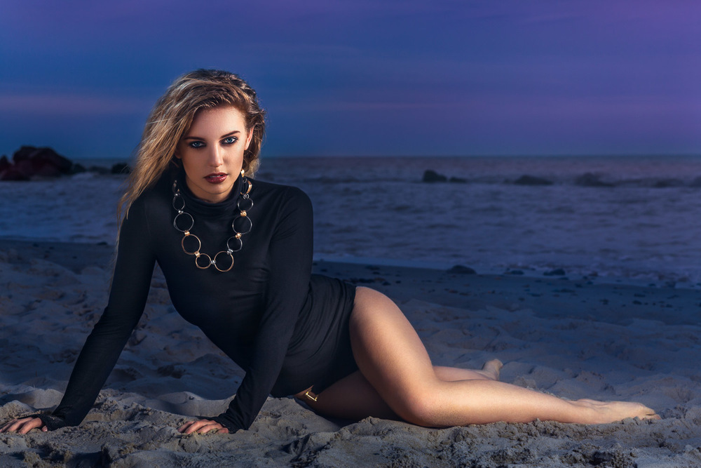 Female model lying on Happisburgh beach at sunset wearing Aurum jewellery necklace