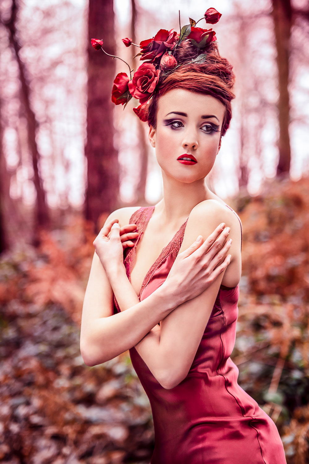 Female model dressed as a red rose wearing a red dress in an enchanted forest with a rose flower headpiece