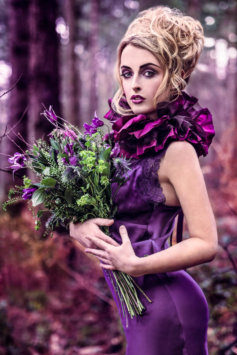 Female model dressed as a purple rose wearing a purple dress with purple flowers in an enchanted forest